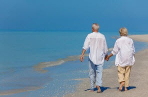 retired couple walking on a beach
